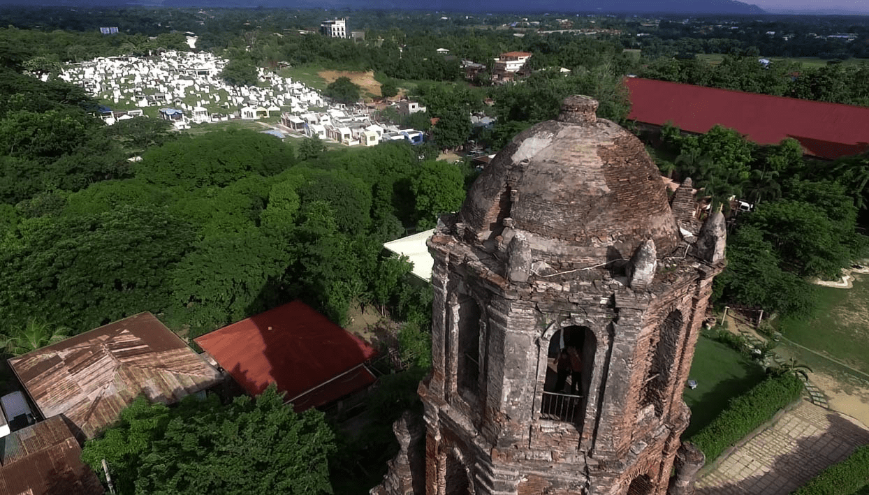 bantay belfry watchtower in vigan city ilocos sur philippines by drone with graveyard on background