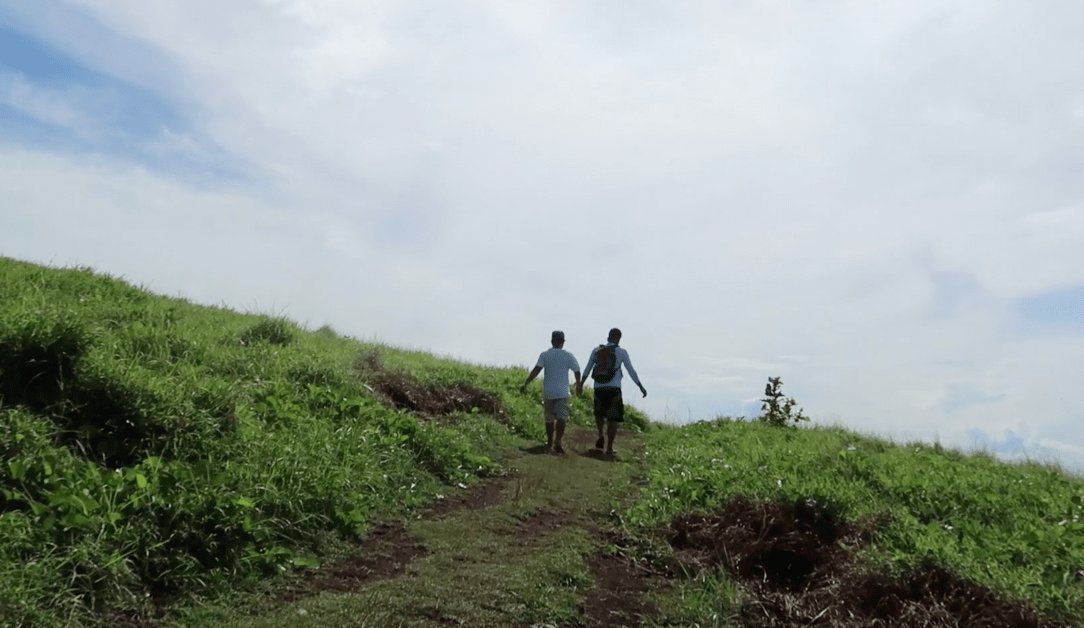 two filipino boys holding hands on a trail on a grassland in the philippines. Point Binurong natural landmark and landscape.