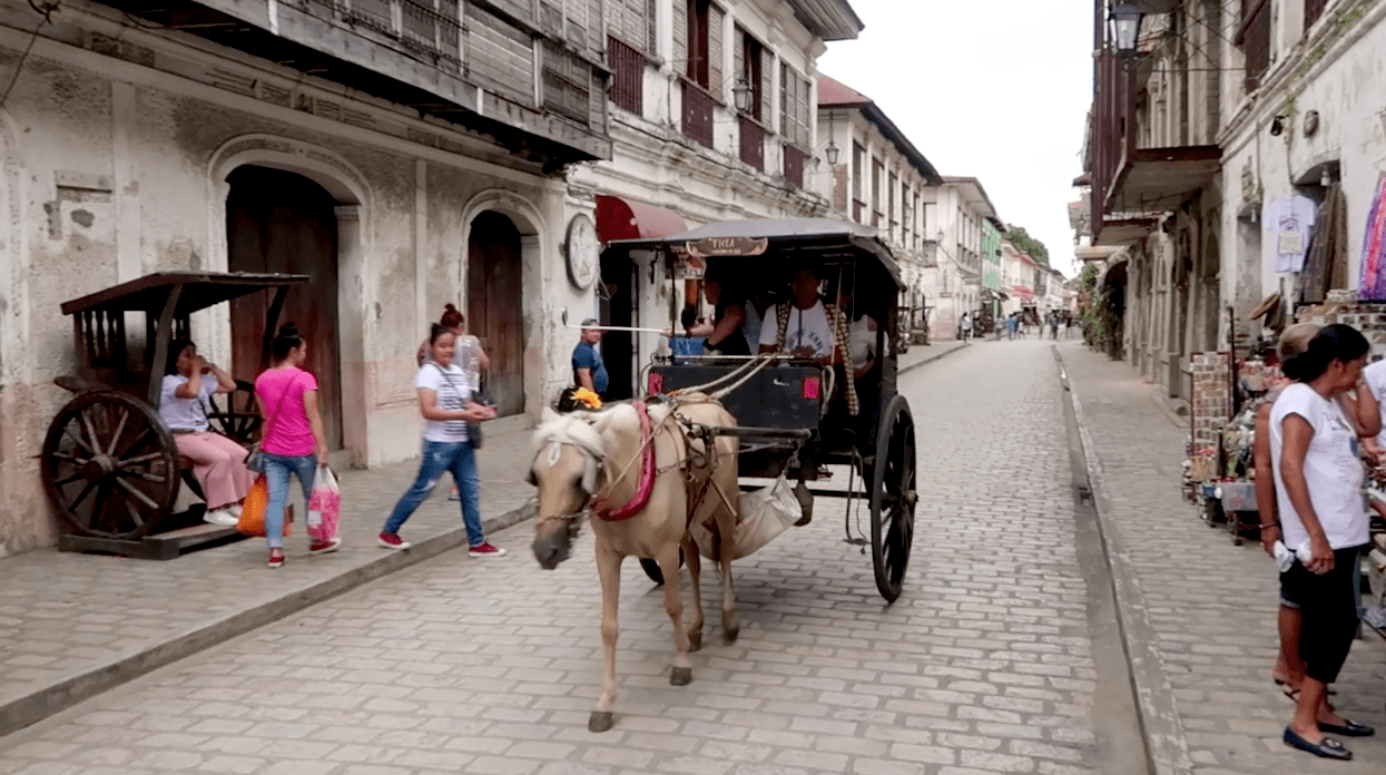 kalesa horse carriage riding through the calle crisologo famous touristic street in vigan city ilocos sur philippines