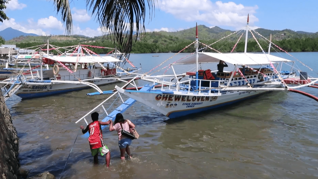 filipina girl stepping into boat in the philippines as part of the honda bay island hopping tour in puerto princesa palawan