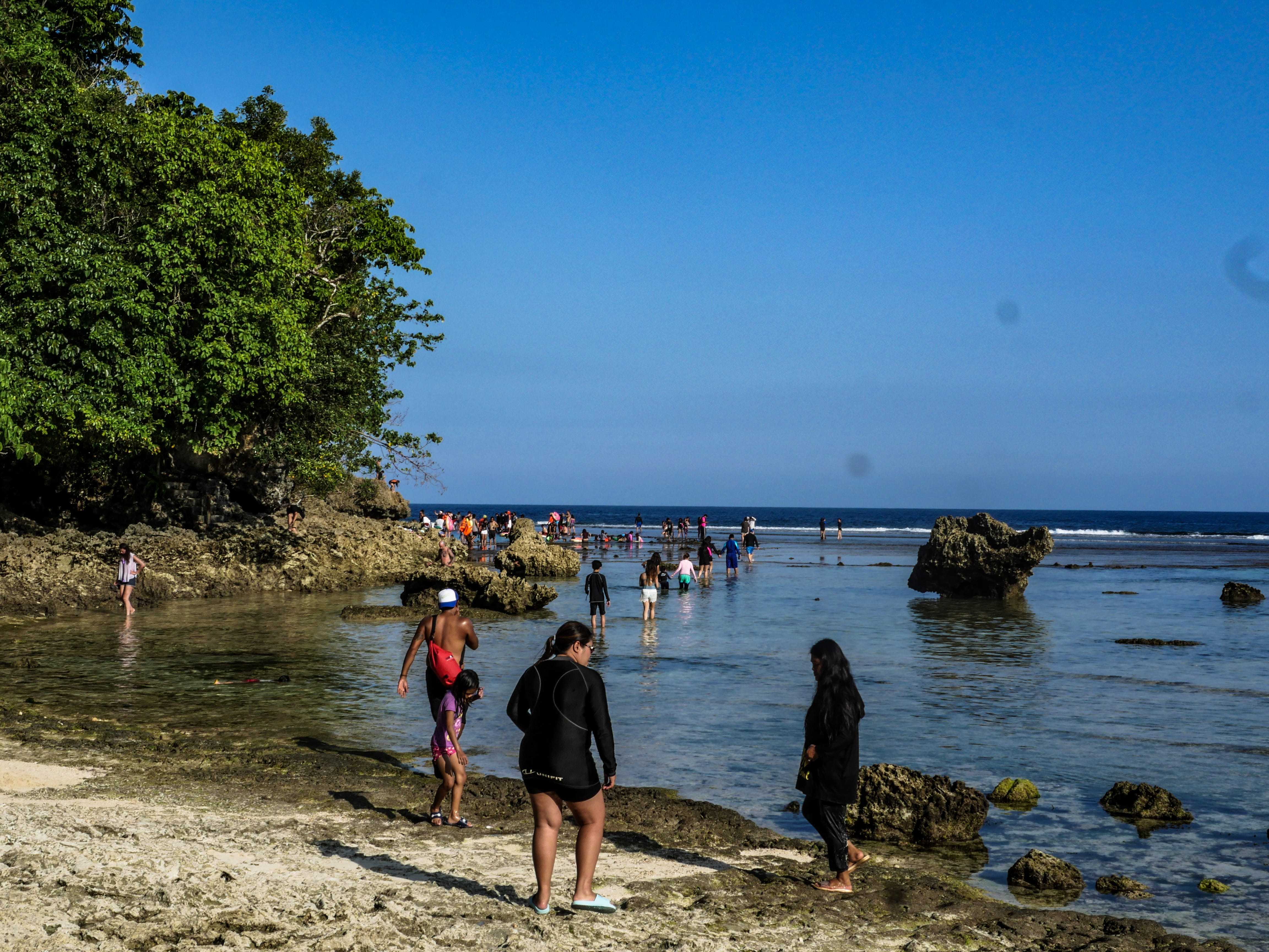 people walking over a trail towards the magpupungko rock pools in siargao island