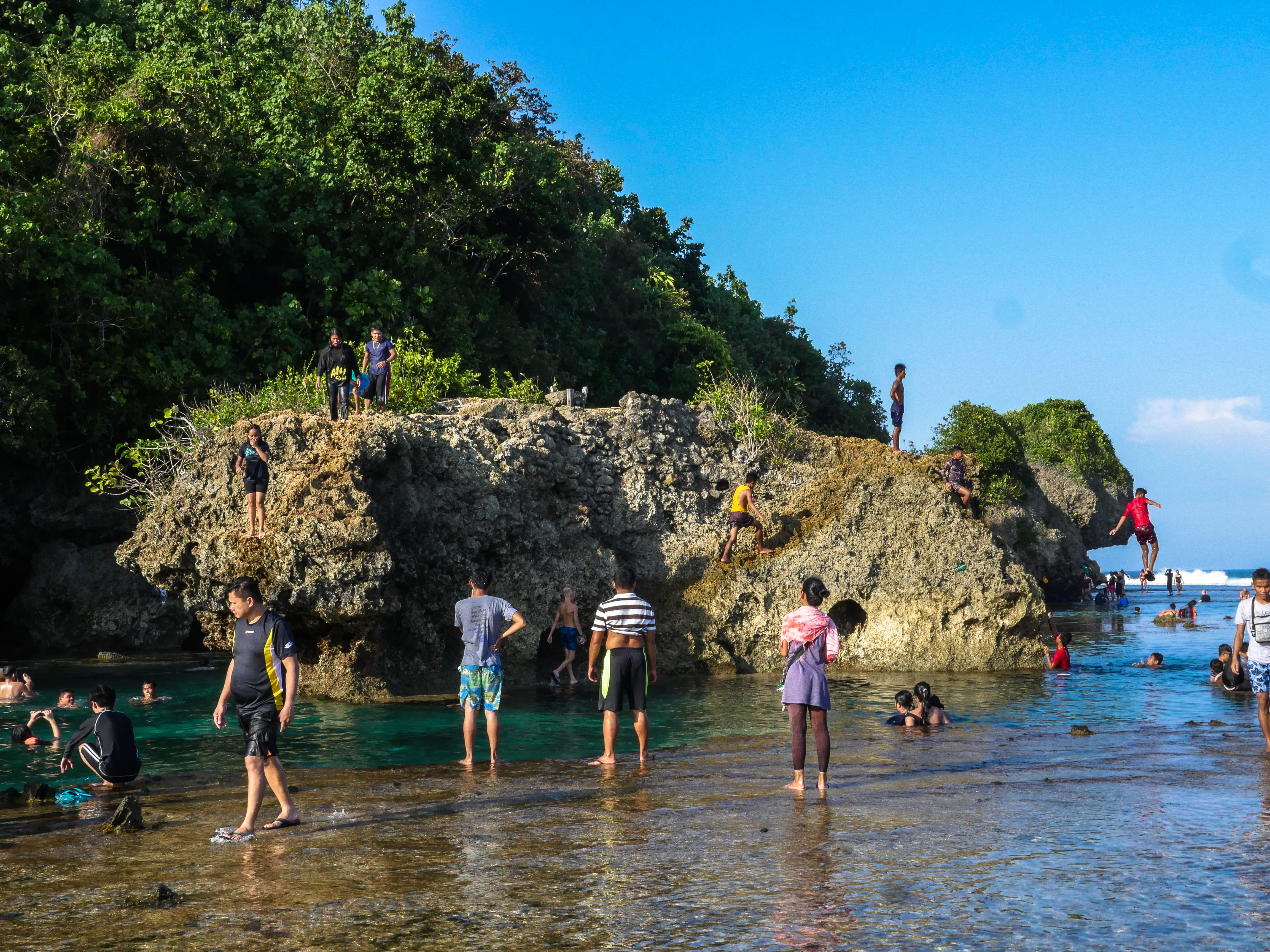 people amusing themselves at magpupungko rock pools and cliff jumping in siargao island