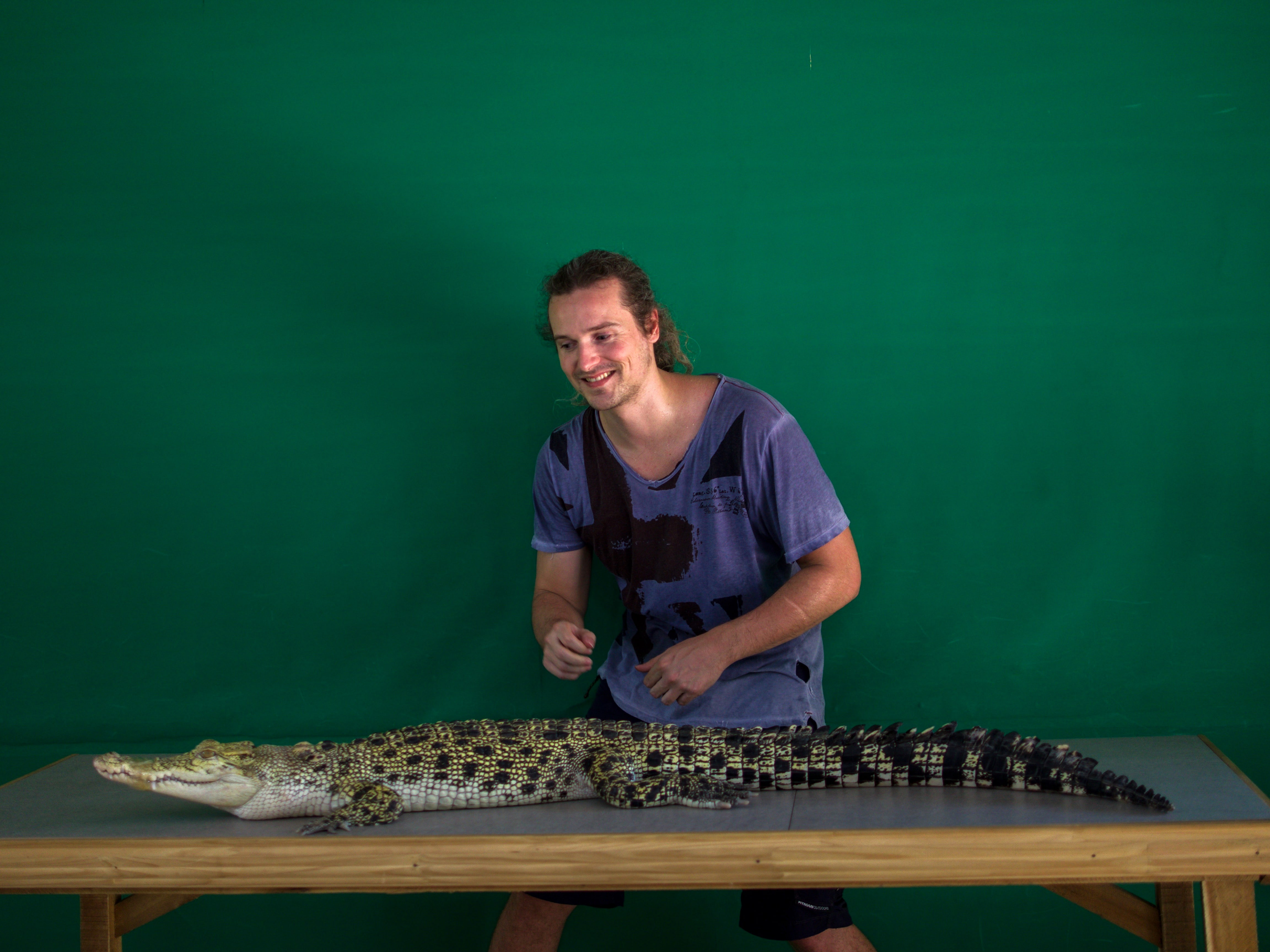 lenny through paradise grabs and poses for photo with little crocodile at Palawan Wildlife Rescue and Conservation Centre