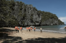 toursits with red life jackets stepping on to the beach at puerto princesa underground river national park in palawan philippines