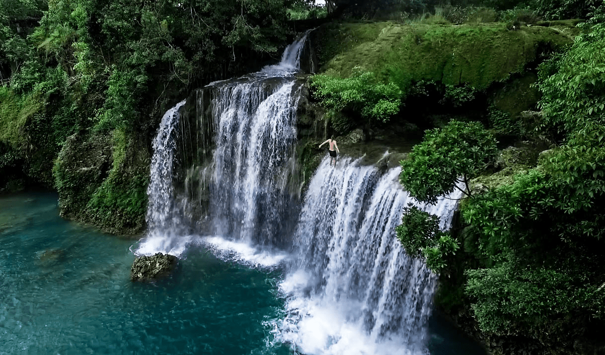 drone photo of lenny through paradise about to jump off the bolinao falls waterfall in pangasinan philippines