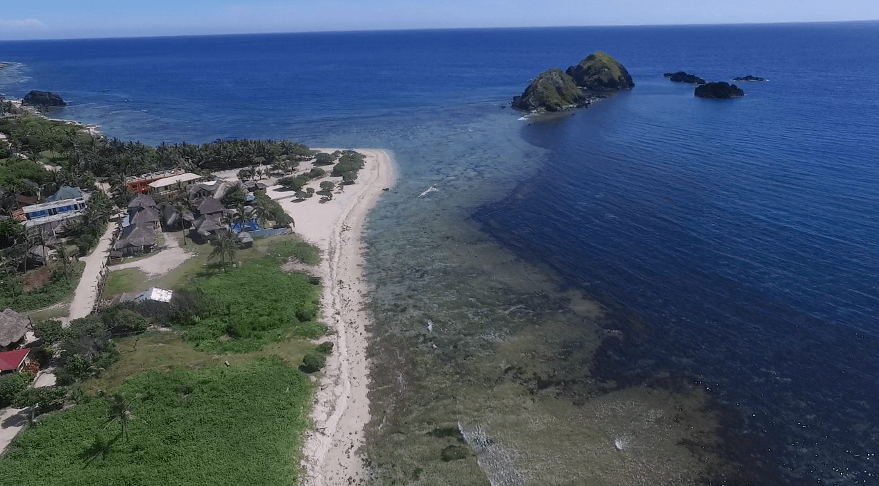 Blue Lagoon Beach in Pagudpud Ilocos Norte as seen from the sky by drone footage.
