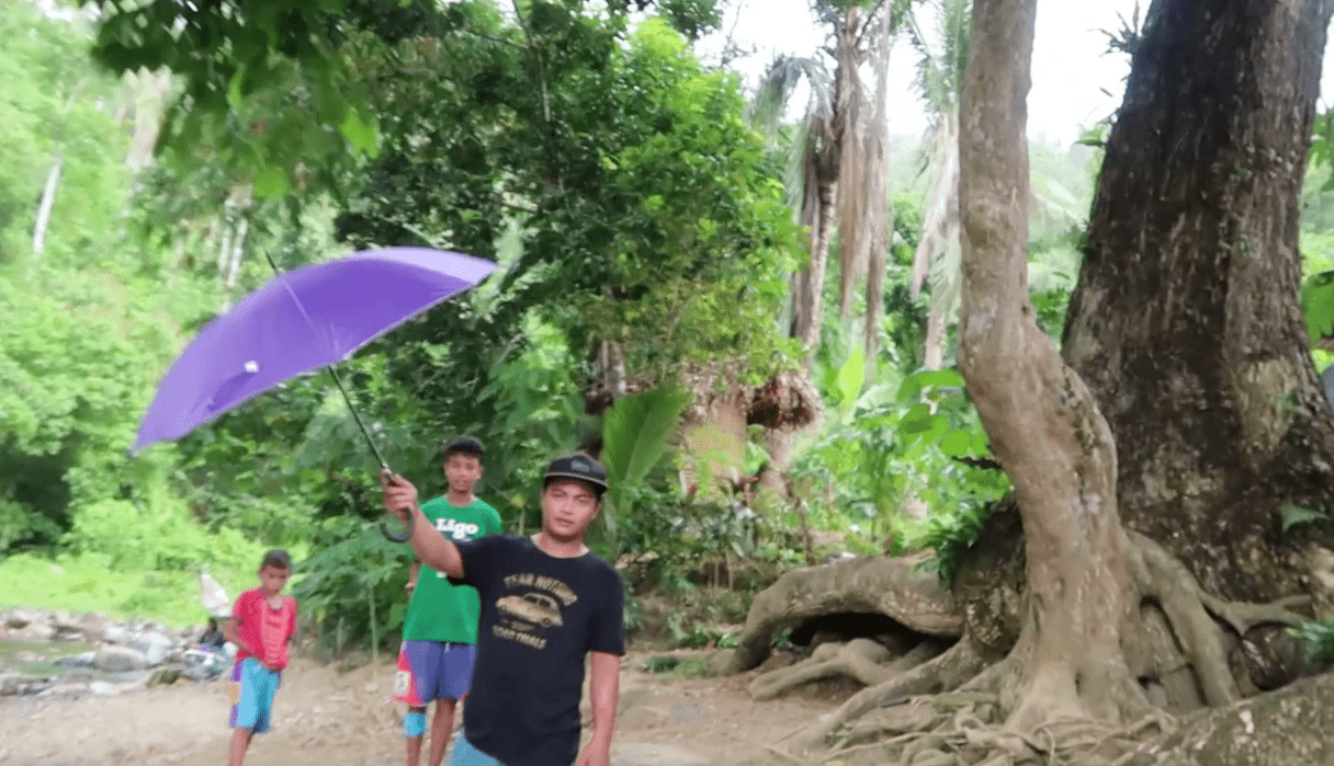 hospitable filipino young man holding umbrella for approacing foreigner in catanduanes province philippines