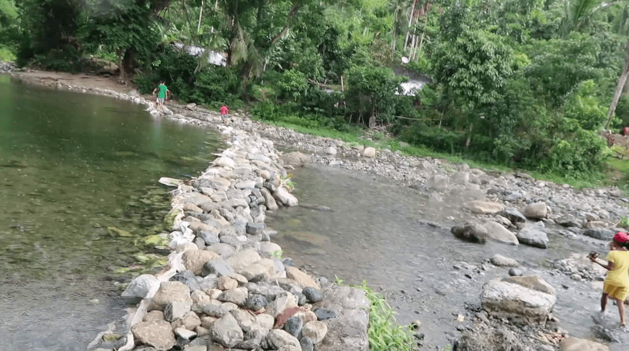 rocky river with filipino kids walking through water in catanduanes province philippines