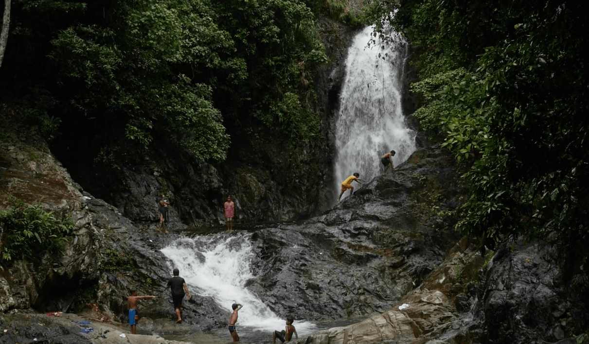 local filipino kids crossing stone bridge in front of the Hicming falls waterfall in catanduanes province philippines