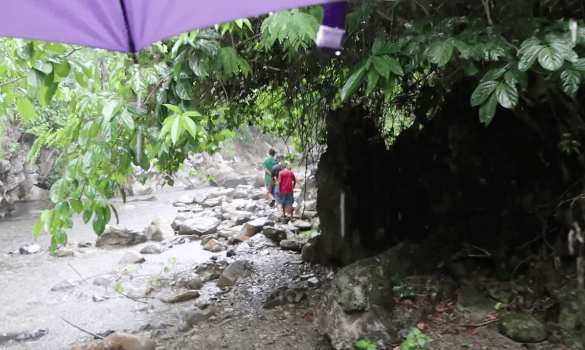 seeing filipino locals walking through the rain at a rocky riverside in the catanduanes province philippines