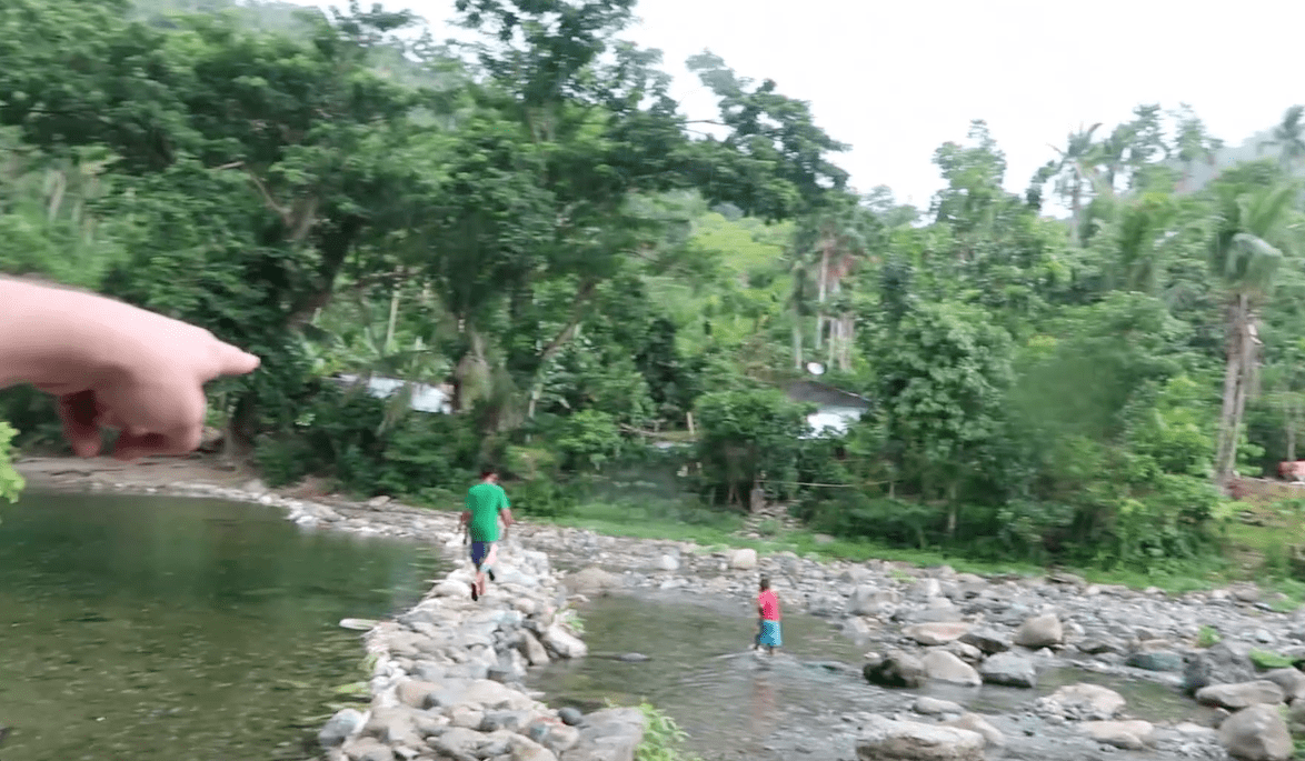 pointing at filipino locals walking over rocks through river in catanduanes province philippines