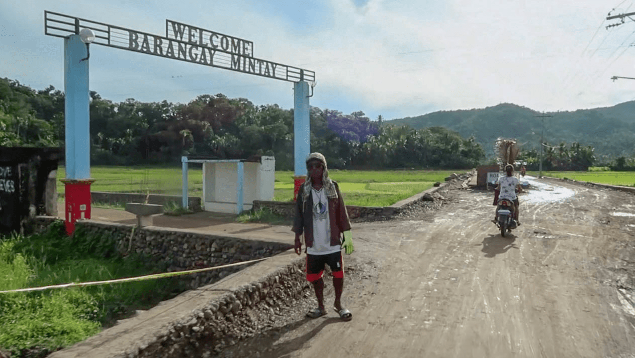 filipino man in front of barangay sign in catanduanes island philippines