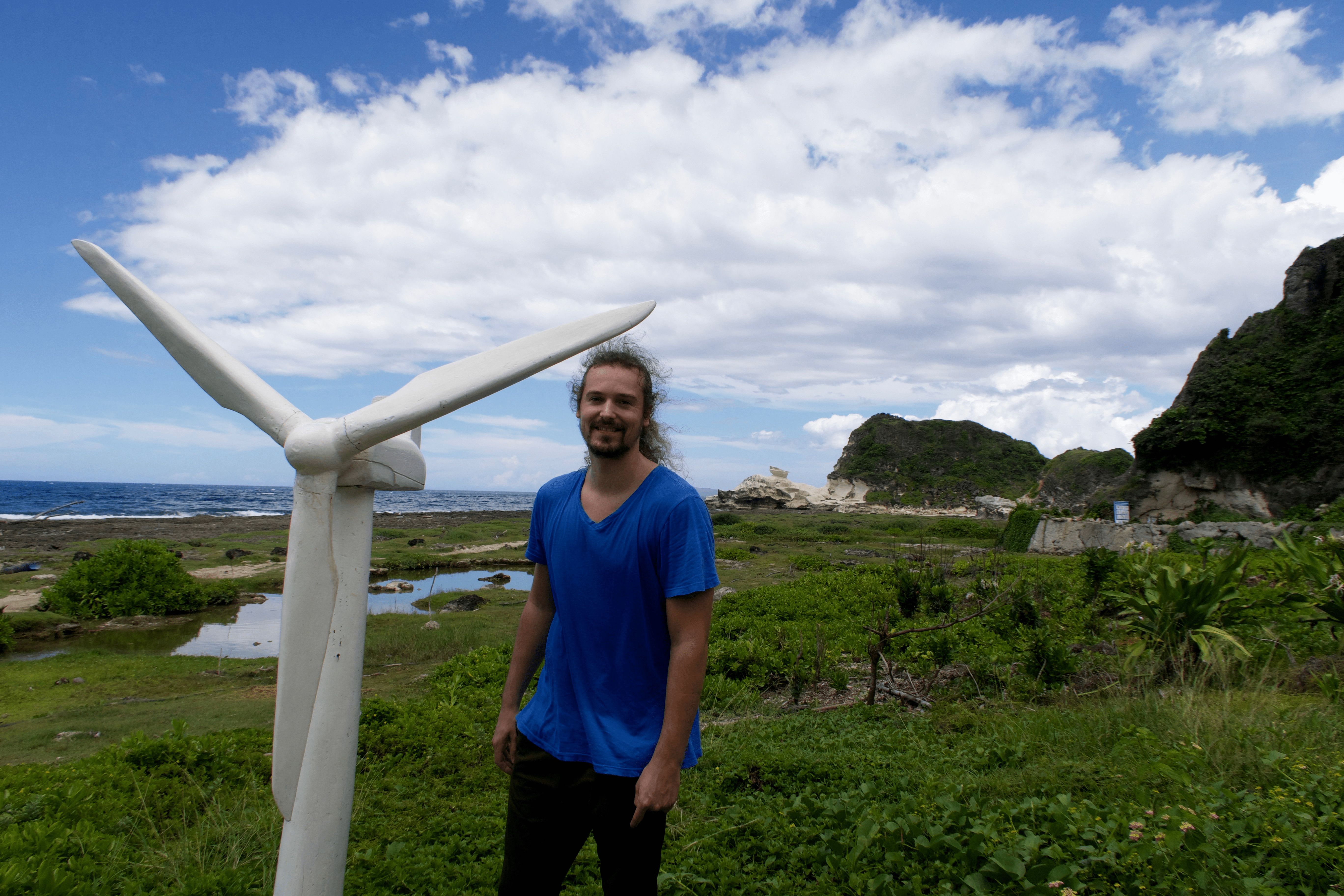 Lenny Through Paradise posing with a mini windmill with the Kapurpurawan rock formation in the background. Pagudpud, Ilocos Norte, Philippines.