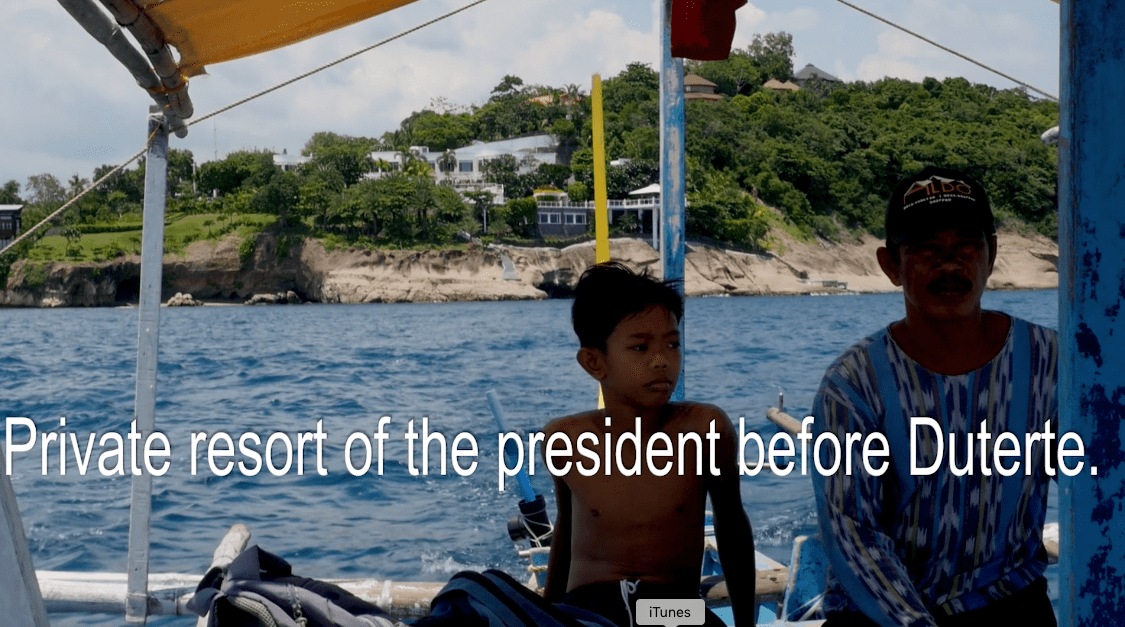Filipino boatmen in Batangas, with the private resort of a former president in the Philippines