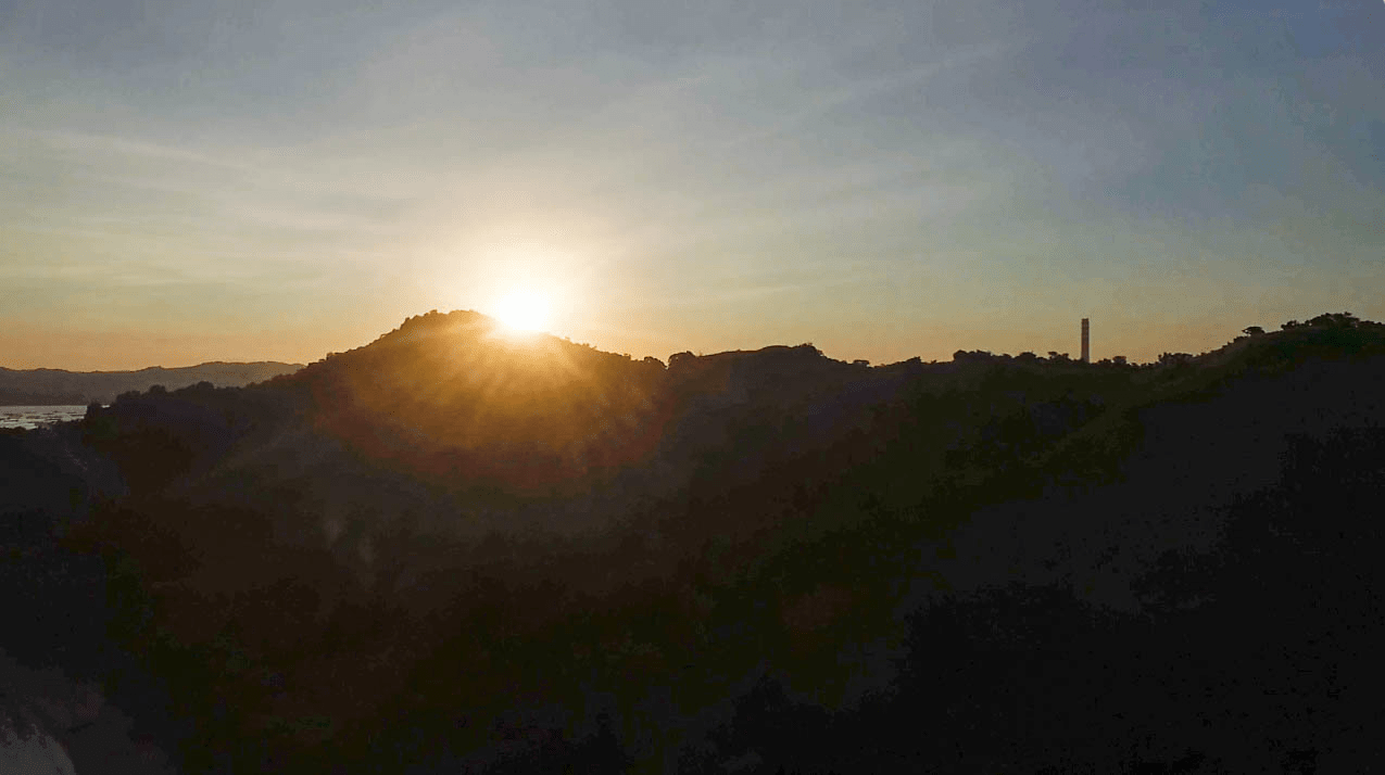 drone photo of sunset behind mountain at cabalitian island in pangasinan province philippines