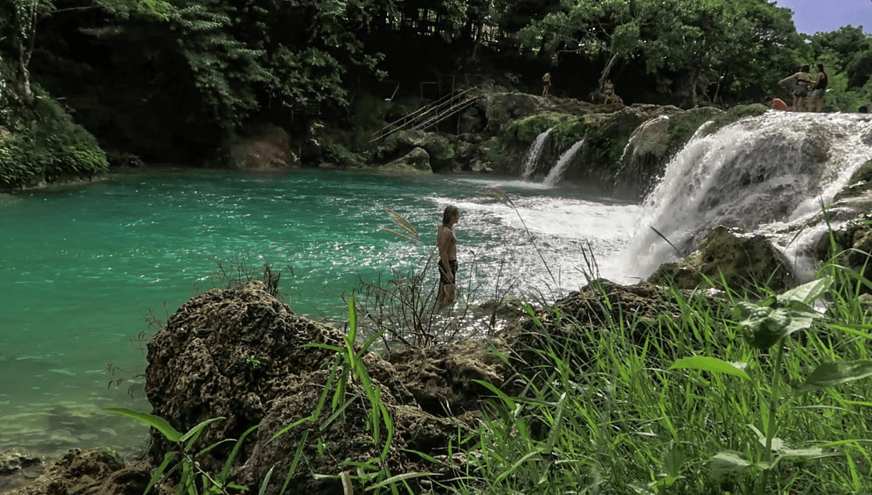 lenny through paradise standing in the water at bolinao falls waterfall two in pangasinan province philippines