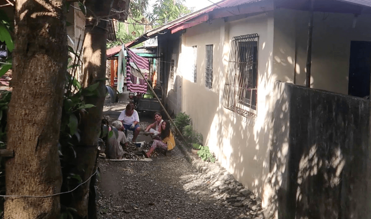 filipino family eating in alley in typical barangay in the philippines