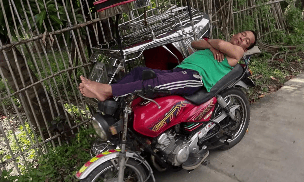 filipino man sleeping on top of his tricycle  in a typical barangay in the philippines