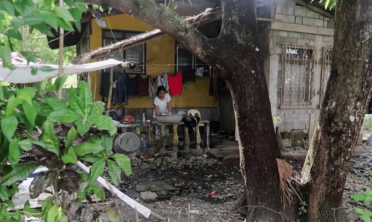 filipino woman washing clothes outside in a typical barangay in the philippines