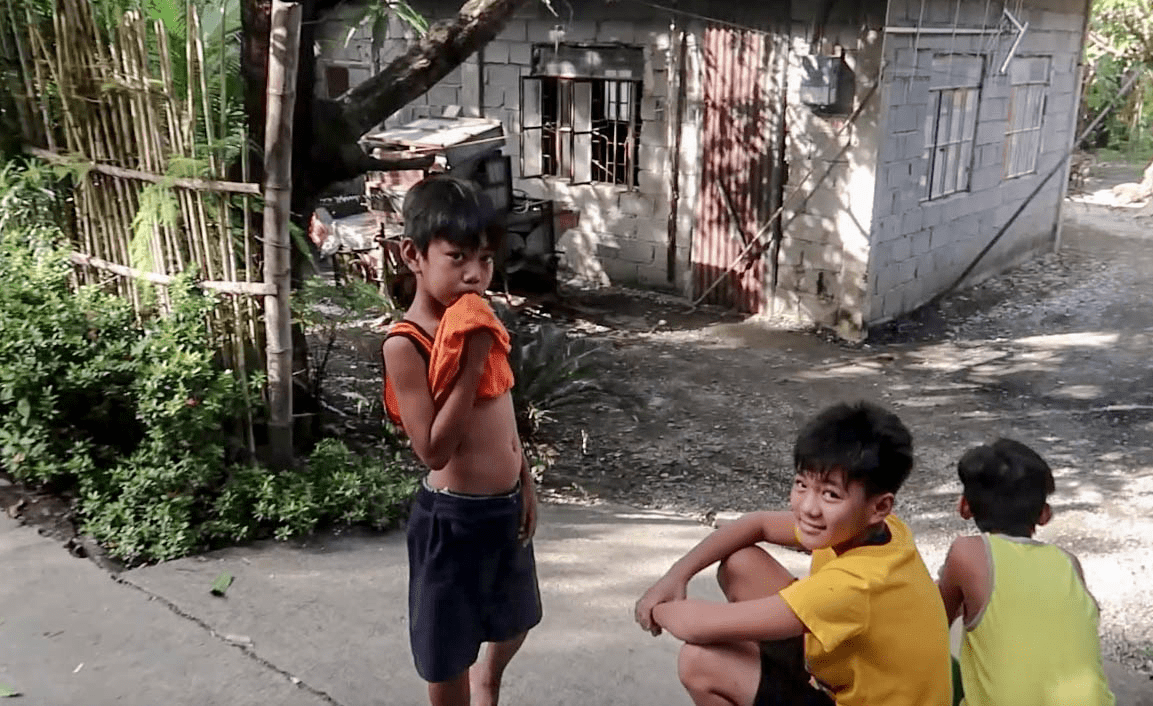shy filipino boys smiling to foreigner in a typical barangay in the philippines