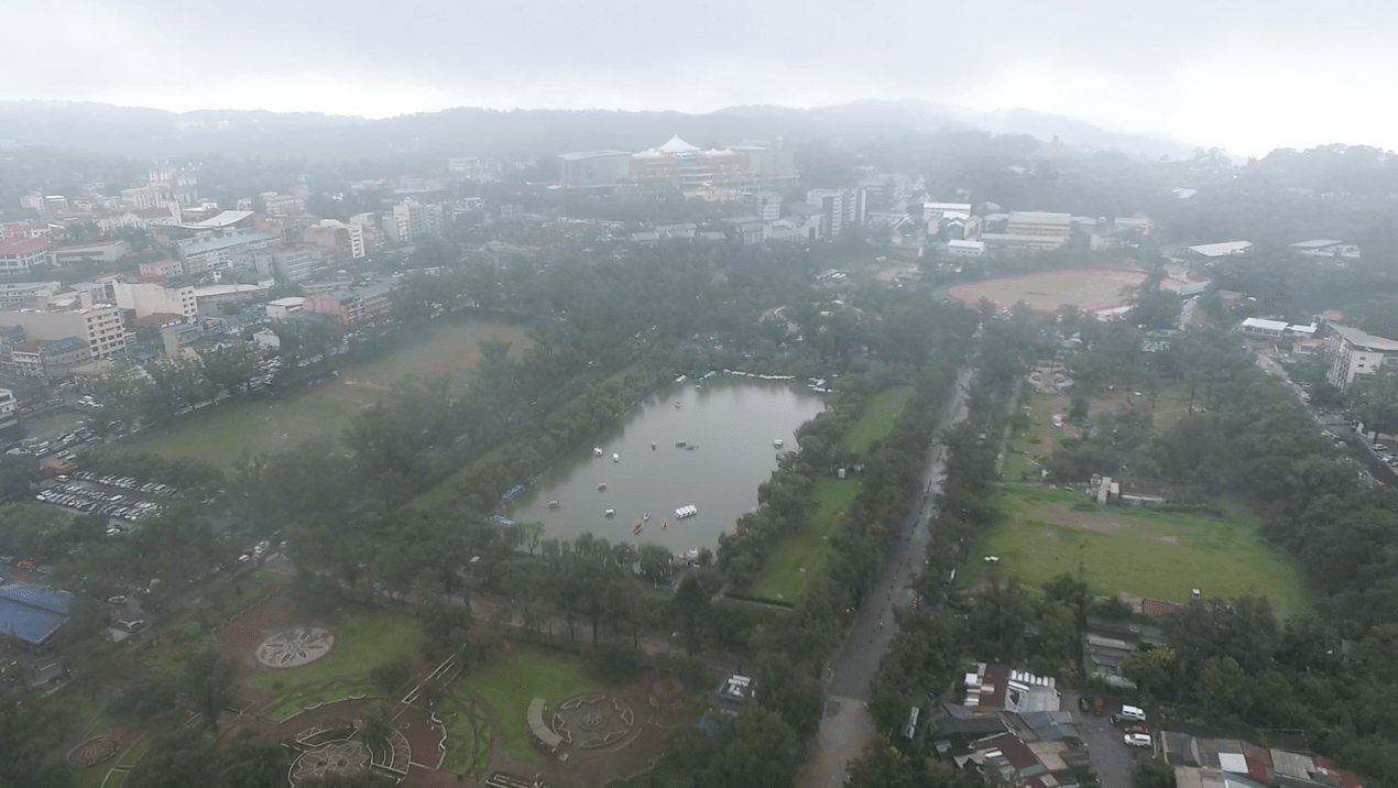 Baguio City Philippines from above drone shot with a cloudy rainy horizon.