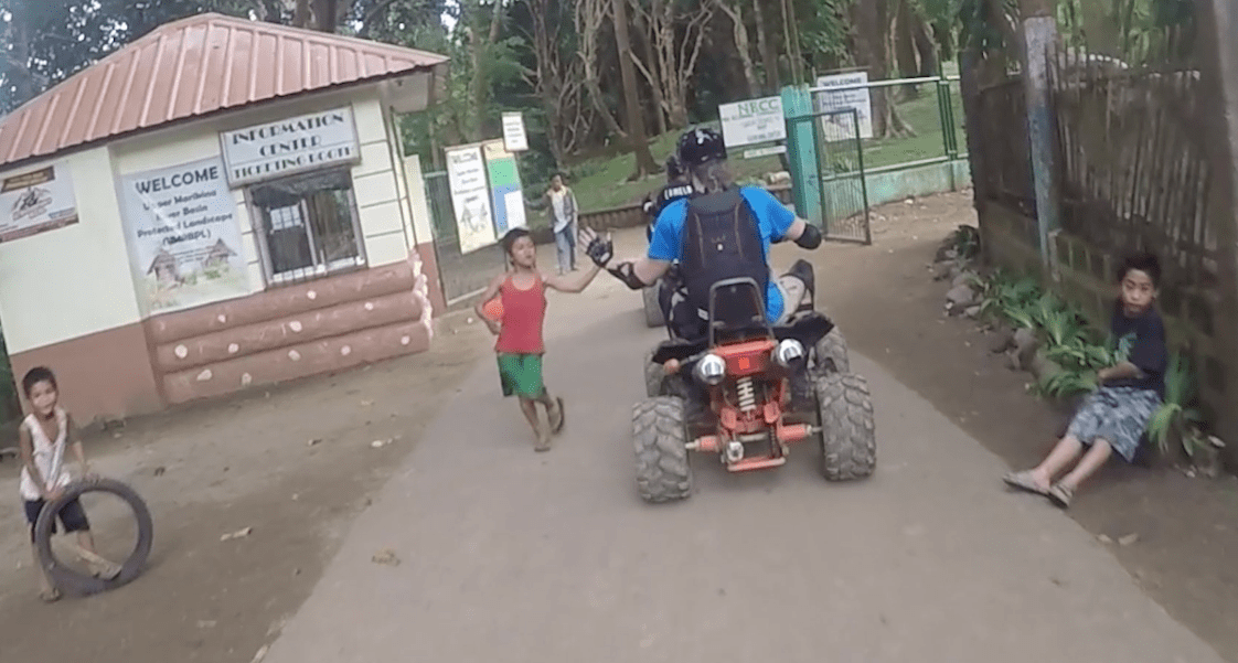 high five with local filipino kid while quad riding